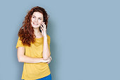 Pleasant communication. Joyful attractive young woman smiling and having a phone conversation while standing against blue background