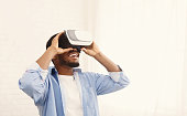Joyful african-american man using VR headset and experiencing virtual reality at home, copy space