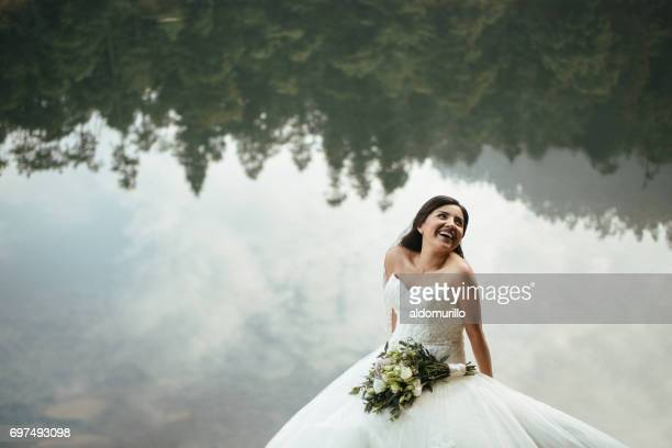 Joyful bride smiling away with lake in background