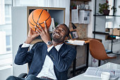 Playful mood. Cheerful young african manager in suit is sitting in office and holding orange basketball with smile. He is looking up while being ready to throwing it