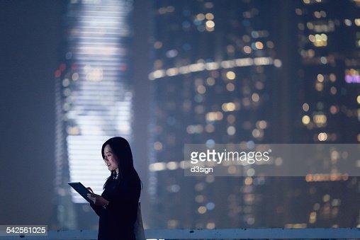 Joyful businesswoman using digital tablet in city : Stock Photo