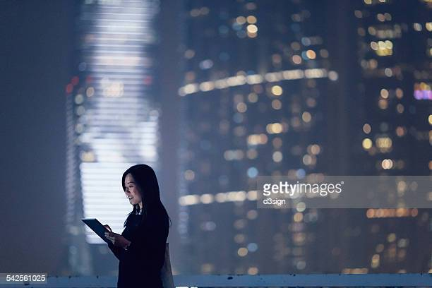 Joyful businesswoman using digital tablet in city