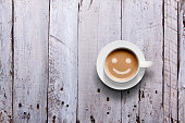 An overhead studio shot of a coffee mug with a smile in the coffee froth, on a rustic wooden background.
