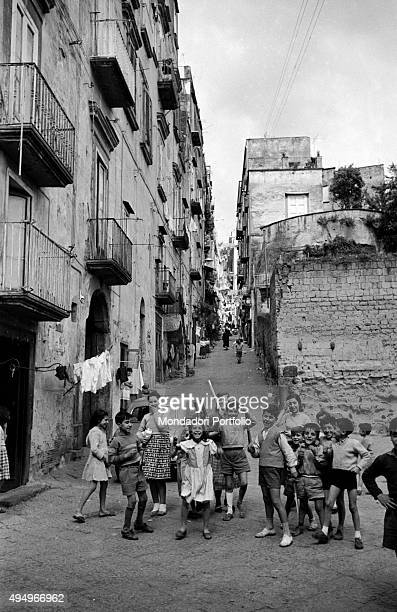 A joyful company of kids of different ages at the foot of a sloping alley in the Old Town one of them in short pants brandishes a wooden sword having...