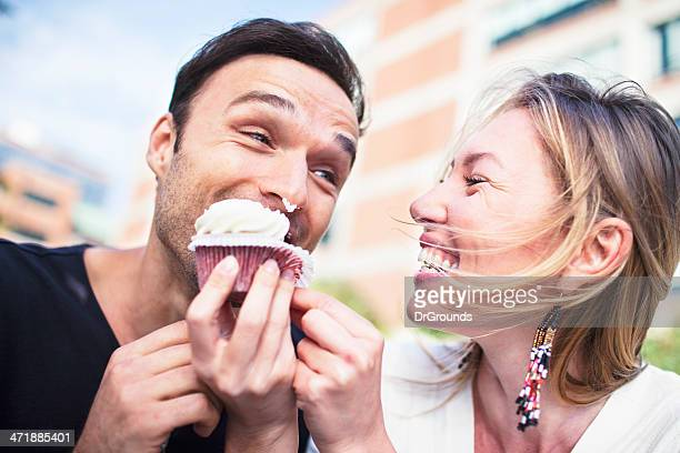 Joyful couple eating cupcake outdoors