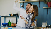 Crazy couple have fun dancing and singing in the kitchen at home in the morning