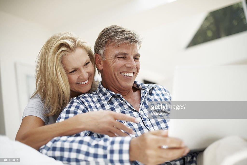 Joyful couple looking at a laptop at home : Stock Photo