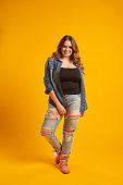 Full-length portrait of joyful curvy girl in casual outfit posing at studio