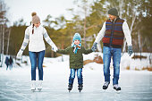 Family portrait of cheerful young parents looking at their son with smile and holding his hands while skating on winter park rink, blurred background