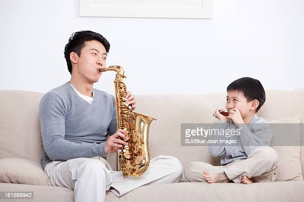 Joyful father and son playing saxophone and harmonica at home