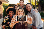 Happy young friends having fun at party taking selfie. Focus on mobile phone in hands of female.