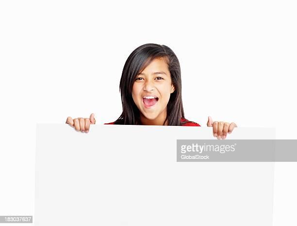 Alegre Menina segurando um cartaz branco isolado