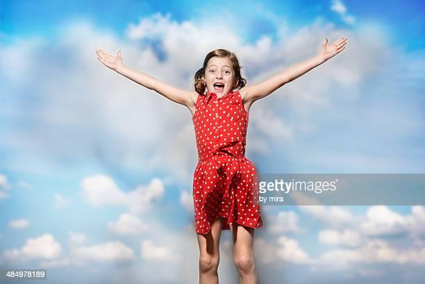 joyful girl jumping on the background of blue sky
