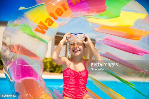 Joyful Girl Relaxing In The Swimming Pool Inside The Inflatable Water Wheel