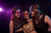Three Asian girl in masquerade masks having fun in night club