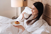 Wonderful mood. Joyful happy attractive woman lying in her bed and having tea with a cake while being in a wonderful mood
