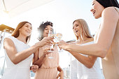 Hen party. Joyful happy young women standing together and cheering with champagne while having a celebration