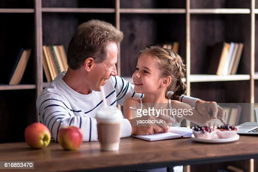 Joyful little girl drawing with her grandfather : Stock Photo