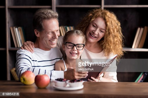 Joyful little girl reading with her grandparents : Stock Photo