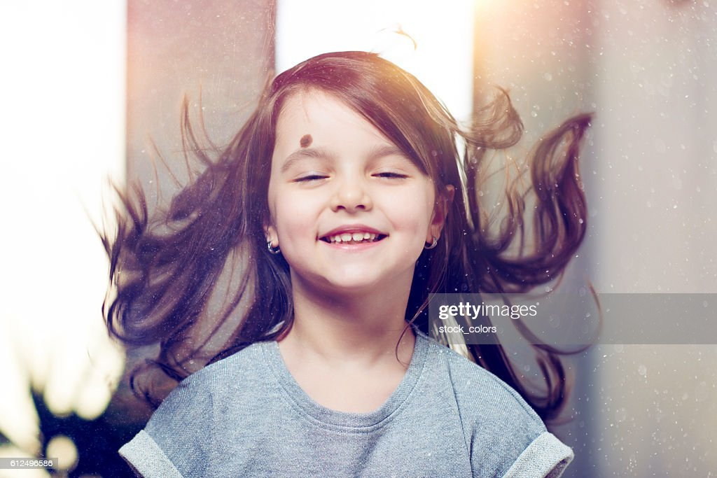 joyful little girl with flying hair : Foto stock