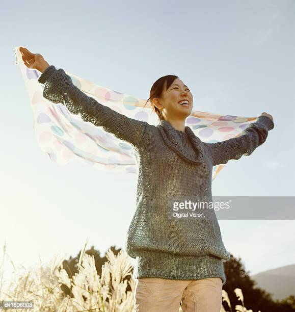 Joyful Looking Woman Holding Out a Spotted Piece of Fabric Behind Her