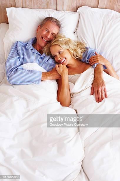 Fröhlich mittleren Alter Paar in einem Schlafzimmer liegen ganz wie zu Hause fühlen.