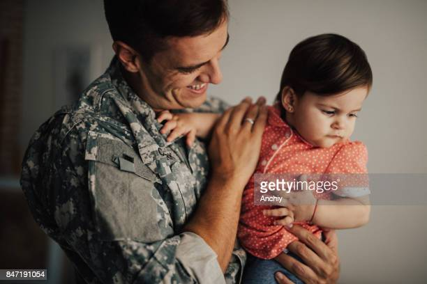 Joyful military dad holding his little baby for the first time