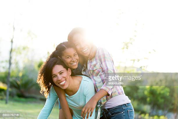 Joyful mother and daughters smiling outdoors in backlight