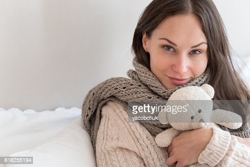 Joyful positive woman hugging a teddy bear : Foto de stock