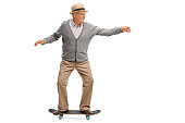 Joyful senior man riding a skateboard isolated on white background
