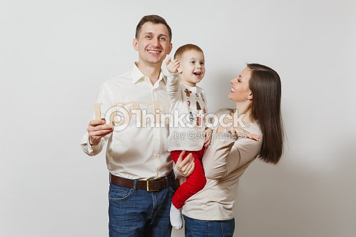 688e9454 Joyful smiling young man, woman holding, hugging little cute child boy with  wooden word Love isolated on white background. Father, mother, little kid  son.