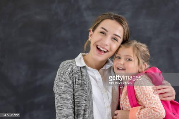 Joyful teacher hugs little girl