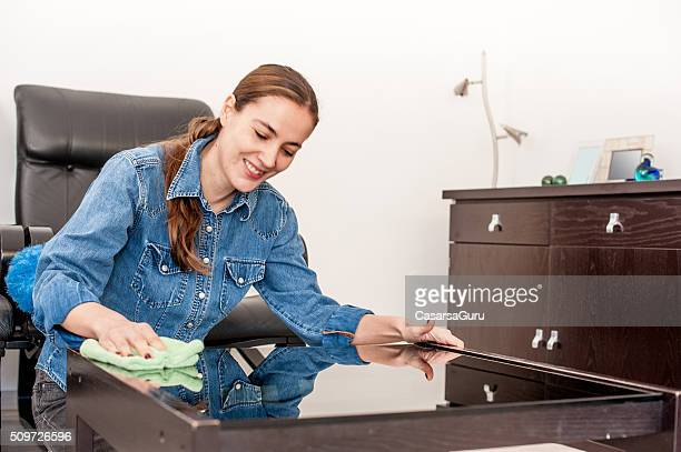 Joyful Woman Cleaning Coffee Table in Living Room