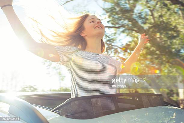 Joyful woman leaning out of a car sunroof
