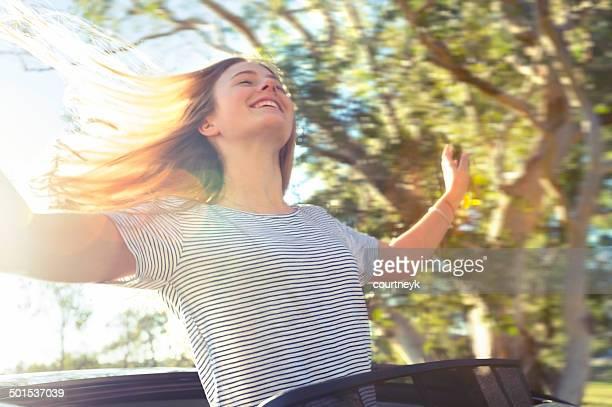 Fröhliche Frau schiefen Sie ein Auto Sonnendach
