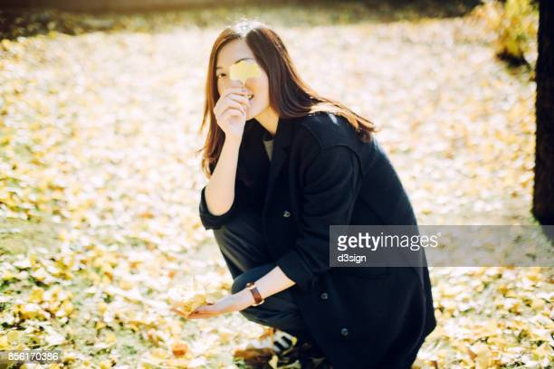 Joyful woman picking up a handful of fallen gingko leaves and having a great time in the park