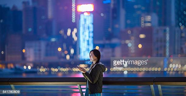 Joyful woman using smartphone in city looking away