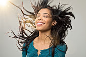 Closeup of smiling young woman blowing her hair in the wind