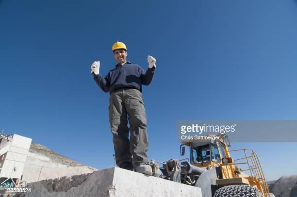 joyful worker on top of marble slab in quarry