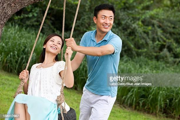 Joyful young couple playing on a swing