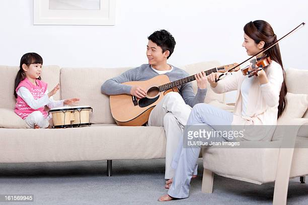 Joyful young family playing musical instruments at home