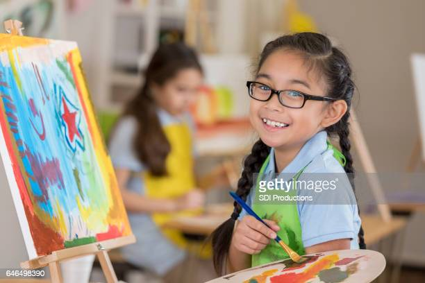 Joyful young female art student paints in a studio