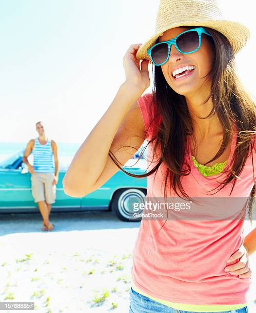 Joyful young girl and a man leaning on his car