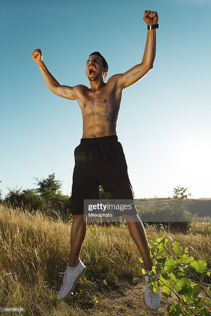 Joyful young man jumping after training in nature : Stock Photo