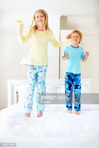 Joyful, young sister and brother jumping on bed