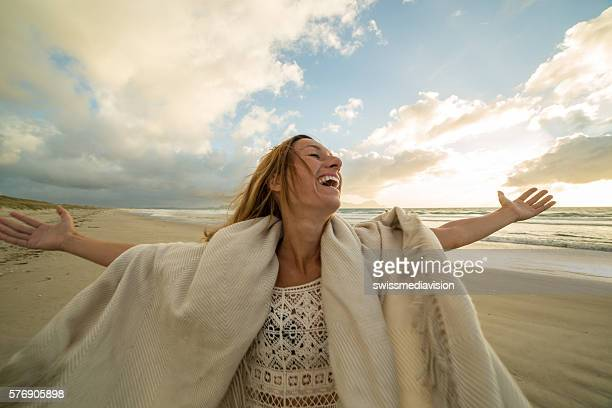 Joyful young woman arms outstretched on beach at sunset