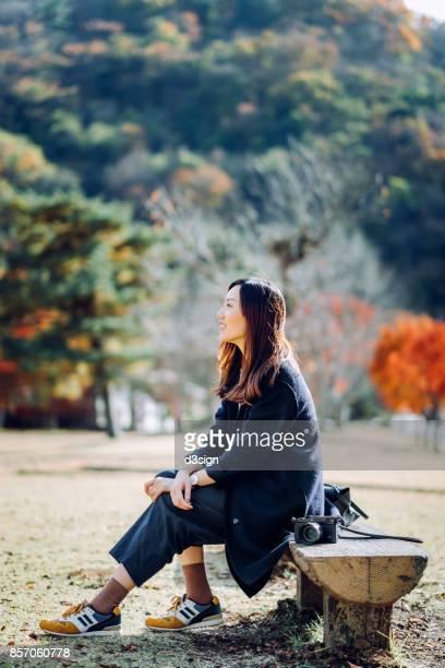 Joyful young woman basking in sunshine and enjoying the beautiful scenics in a nature park