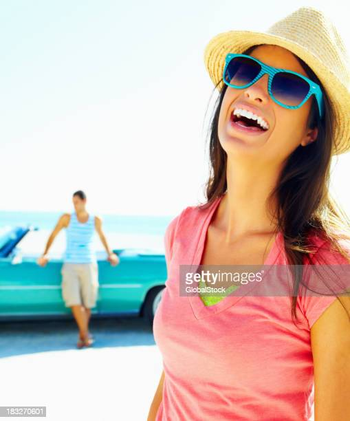 Joyful young woman wearing sunglasses with man in background