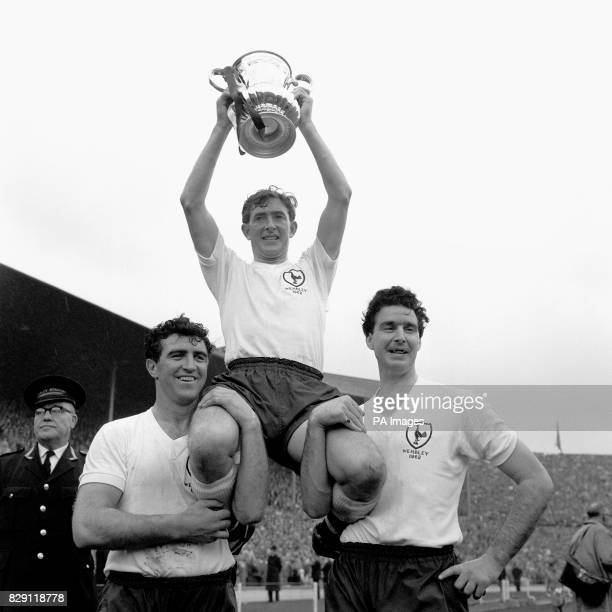 A joyous sight for thousands of Tottenham Hotspur fans at the Empire Stadium Wembley as Spurs righthalf and captain Danny Blanchflower holds up the...