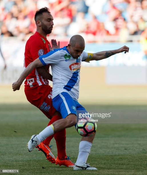 Jozsef Kanta of MTK Budapest shoots on goal before Jose Antonio Delgado Villar 'Nono' of DVTK during the Hungarian OTP Bank Liga match between MTK...